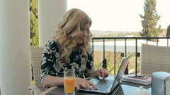 Attractive young woman working at a laptop in a cafe on the terrace Stock Footage