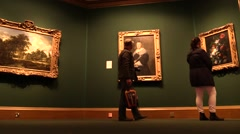 Stock Video Footage of At the art gallery. Visitors observe and contemplate paintings .