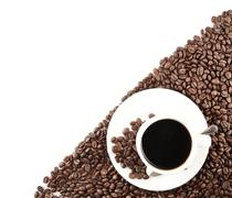 Closeup scattered coffee cup and beans in the corner on white background - stock photo