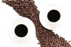 Coffee beans arranged diagonally with coffee cups isolated on white backgroun - stock photo