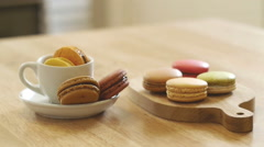 French macarons in white cup and on wooden tray. Stock Footage