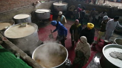Local people preparing food in large kettles in public kitchen in Amritsar. Stock Footage