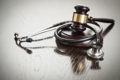 Gavel and Stethoscope on Reflective Wooden Table. - stock photo