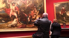 At the art gallery. Visitors photographing paintings with smartphones Stock Footage