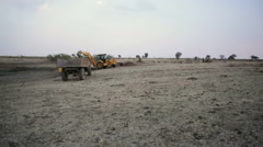 Earthworks with bulldozers and trucks, long shot, pan left - stock footage