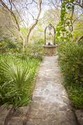 Stock Photo of Beautiful Lush Park Walkway and Antique Well with a Variety of Foliage.