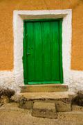 Old wooden door with access steps on adobe house Stock Photos