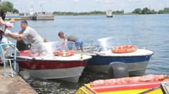 Motor boats are moored at the shore of the Dnieper River. Passengers are loaded  Stock Footage