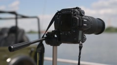 The camera is on a tripod pointing into the distance across the river - stock footage