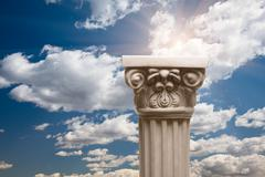 Ancient Replica Column Pillar Over Dramatic Clouds and Sunburst. - stock photo