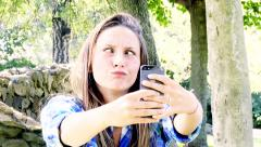 Cute blonde teenager taking selfie making funny face in park closeup Stock Footage