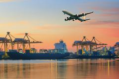 Cargo plane flying above ship port use for transportation and freight logisti Stock Photos