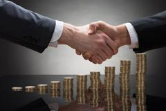 Close-up Of Two Businessmen Shaking Hands With Stack Of Coins Stock Photos