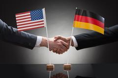 Close-up Of Two Businesspeople Shaking Hands In Front Of Us And Germany Flags - stock photo