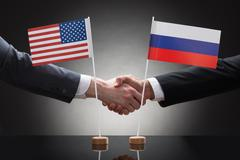 Close-up Of Two Businesspeople Shaking Hands In Front Of Us And Russia Flags  Stock Photos