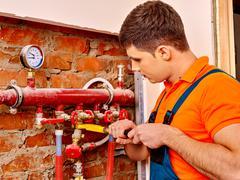 Men builder fixing heating system Stock Photos