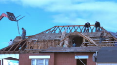 Demolition/construction crew tears the roof off an old house for remodeling - stock footage