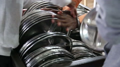 People arranging pile of silver plates at public kitchen in Amritsar. Stock Footage