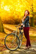 Beauty girl relaxing in autumn park with bicycle, outdoor Kuvituskuvat