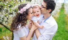 Cheerful parents kissing their beloved child - stock photo