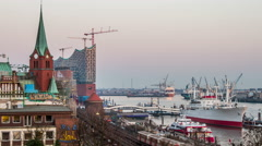 Philharmonic building and harbor with container ships in the evening timelapse Stock Footage