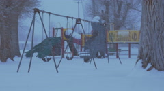 Blowing and driving snow falls on a cold gray empty playground Stock Footage