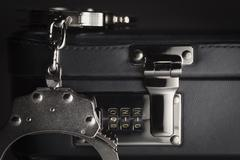 Pair of Handcuffs on Briefcase with the Numbers 911 on Lock. - stock photo