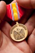 Man Holding National Defense War Medal in The Palm of His Hand. Stock Photos