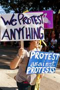 A Protester Against Protests Carries Signs In Oddball Miami Parade - stock photo