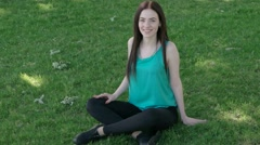 Female sitting with crossed legs on the green grass Stock Footage