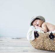 Cute tot sleeping in a basket Stock Photos