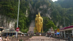 Batu Caves entrance steps and tall Murugan statue, panning shot Stock Footage