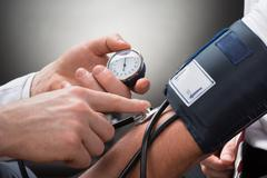 Close-up Of A Doctor's Hand Checking Blood Pressure Of A Patient - stock photo