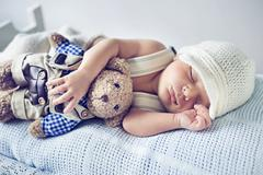 Newborn child sleeping with a teddy bear Stock Photos