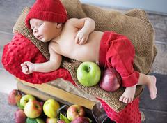 Newborn child sleeping on the box of apples Stock Photos