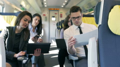 Businesspeople working together in the train while traveling, steadycam shot Stock Footage