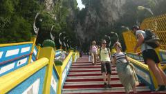 Climb up staircase to Batu Caves entrance, european tourists come down Stock Footage