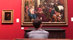At the art gallery. Visitors observe and contemplate paintings . Stock Footage