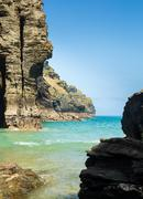 Cliffs jutting into the ocean from Bossiney Haven cove, Cornwall - stock photo