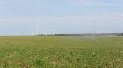 Green field, water sprinkler , wind turbine Stock Footage