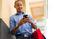 African American Man Text Messaging On Phone With Shopping Bags Stock Photos