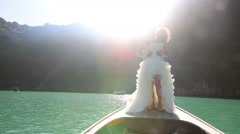 bride and groom kiss standing on longtail boat at backlight - stock footage