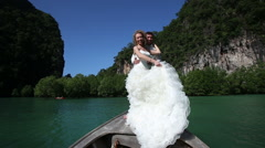 Blonde bride poses and clasps to groom standing on longtail boat Stock Footage