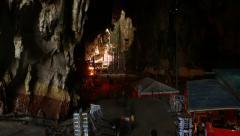 Walking through mystical Batu Caves, dark chamber and bright area ahead Stock Footage