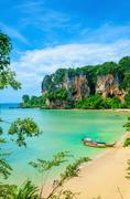 Beach with mogotes and long tail boat, Thailand Stock Photos