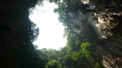 Round gap in cave ceiling, bright sky and green steep sides, full of vegetation Stock Footage