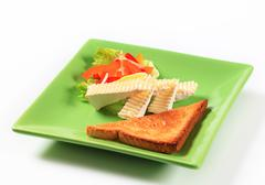 Toasted bread and wedges of white rind cheese Stock Photos