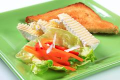 Toasted bread and wedges of white rind cheese - stock photo