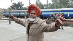 Portrait of man holding his hands widely spread at train station in Amritsar. Stock Footage