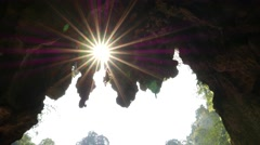 Beautiful sunbeams star through cave vault opening Stock Footage